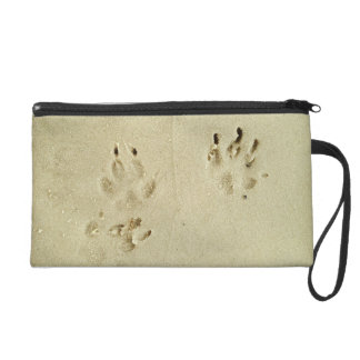 Puppy prints in the sand wristlet clutches