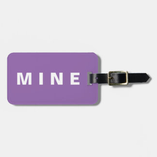 Purple luggage tag with 'Mine' written on it