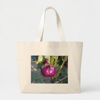 Purple round eggplant hanging on tree large tote bag
