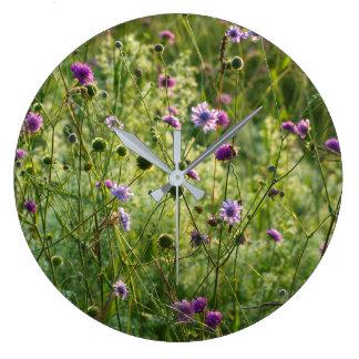 Purple wild flowers in a green meadow large clock