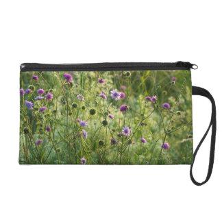 Purple wild flowers in a green meadow wristlet