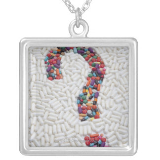 Question mark of pills on white pill background silver plated necklace