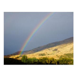 Rainbow dark sky and hillside postcard