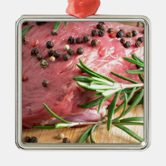 Raw beef with herbs and spices at the kitchen metal ornament