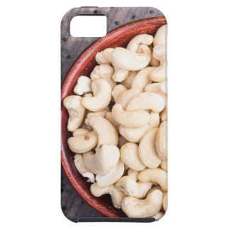 Raw cashew nuts in a brown bowl on fabric iPhone 5 cases