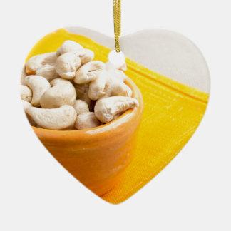 Raw cashew nuts in a small orange cup closeup ceramic heart ornament