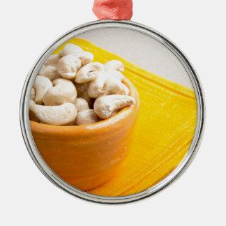 Raw cashew nuts in a small orange cup closeup Silver-Colored round ornament