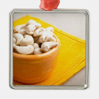 Raw cashew nuts in a small orange cup closeup Silver-Colored square ornament