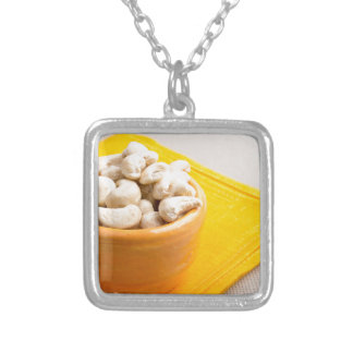 Raw cashew nuts in a small orange cup closeup silver plated necklace