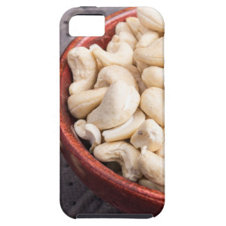 Raw cashew nuts in brown bowl on fabric background case for the iPhone 5