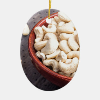 Raw cashew nuts in brown bowl on fabric background ceramic oval ornament