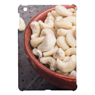 Raw cashew nuts in brown bowl on fabric background iPad mini case