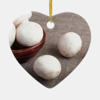 Raw champignon mushrooms and onions ceramic heart ornament