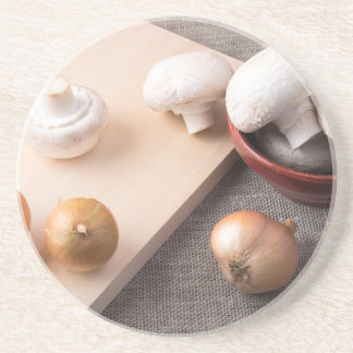 Raw champignon mushrooms and onions on the table beverage coaster