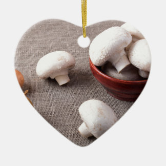 Raw champignon mushrooms and onions on the table ceramic heart ornament