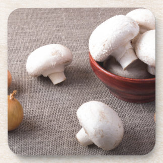 Raw champignon mushrooms and onions on the table coasters