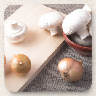 Raw champignon mushrooms and onions on the table drink coasters