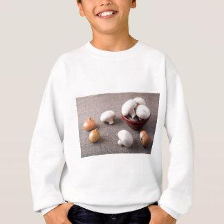 Raw champignon mushrooms and onions on the table sweatshirt