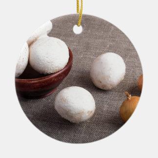 Raw champignon mushrooms and onions round ceramic ornament