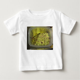 Raw chopped pistachios in a plastic food pan baby T-Shirt