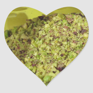 Raw chopped pistachios in a plastic food pan heart sticker