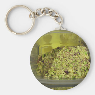 Raw chopped pistachios in a plastic food pan keychain
