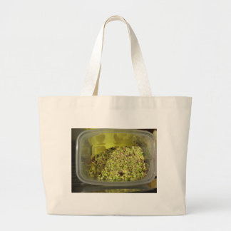 Raw chopped pistachios in a plastic food pan large tote bag