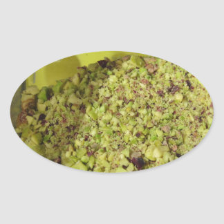 Raw chopped pistachios in a plastic food pan oval sticker