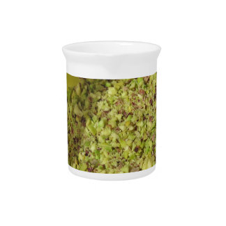 Raw chopped pistachios in a plastic food pan pitcher