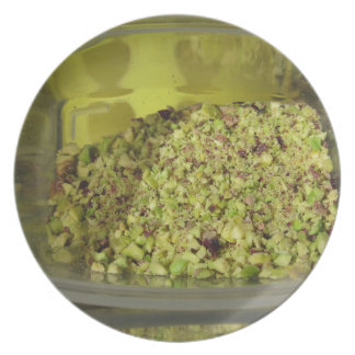Raw chopped pistachios in a plastic food pan plate