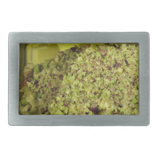 Raw chopped pistachios in a plastic food pan rectangular belt buckle