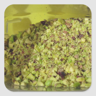 Raw chopped pistachios in a plastic food pan square sticker