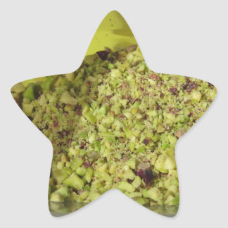 Raw chopped pistachios in a plastic food pan star sticker