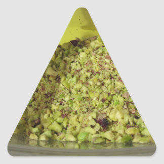 Raw chopped pistachios in a plastic food pan triangle sticker