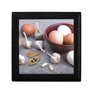 Raw eggs and garlic and spices on the kitchen keepsake boxes