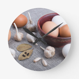Raw eggs and garlic and spices on the kitchen round clock