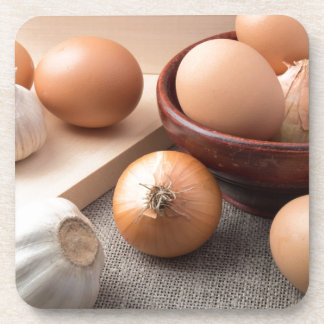 Raw eggs, onions and garlic on a background coaster