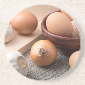 Raw eggs, onions and garlic on a background drink coasters