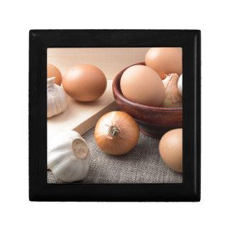 Raw eggs, onions and garlic on a background keepsake box
