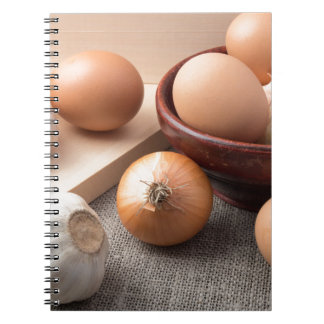Raw eggs, onions and garlic on a background notebook