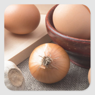Raw eggs, onions and garlic on a background square sticker