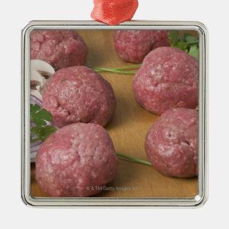 Raw meatballs on a cutting board metal ornament