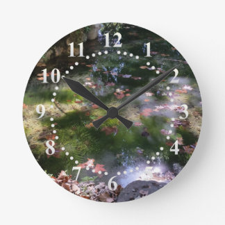 rays and leaves on water round clock