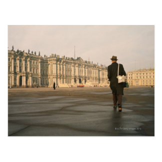 Rear view of a man walking in front of a palace, postcard