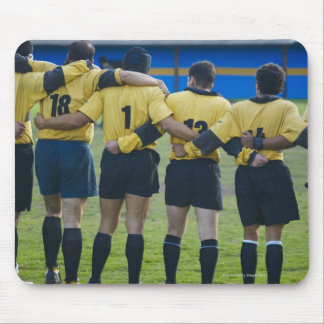 Rear view of rugby team standing with their arms mouse pads
