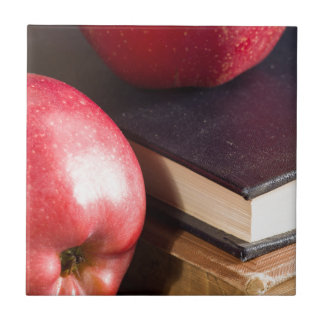 Red apples and old vintage book tile