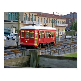Red electric streetcar on tracks postcard