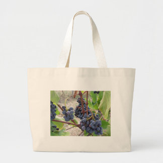 Red grapes on the vine with green leaves large tote bag
