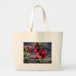 Red Hollyhocks in a summer garden Large Tote Bag