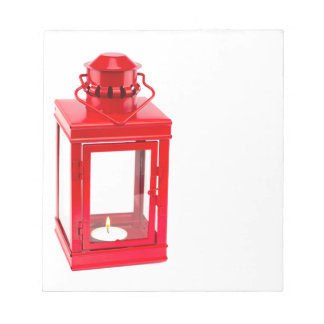 Red lantern with burning tealight on white notepad